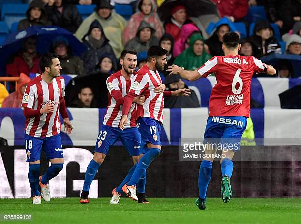 Sporting Gijon's midfielder Carlos Carmona celebrates a goal with teammates during the Spanish league football match Real Madrid CF vs Real Sporting...