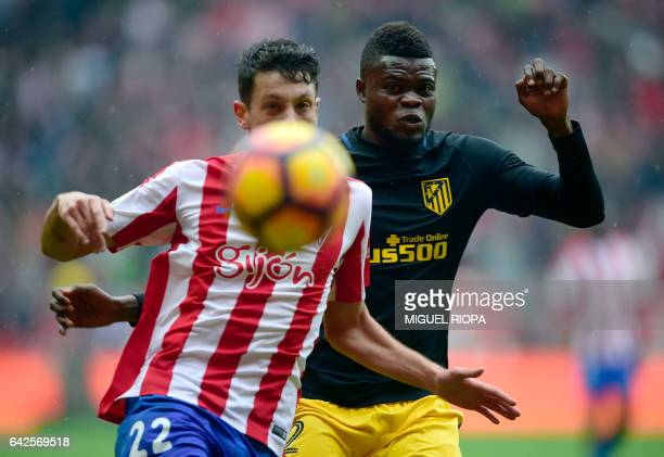 Sporting Gijon's midfielder Mikel Vesga vies with Atletico Madrid's Ghanaian midfielder Thomas Partey during the Spanish league football match Real...