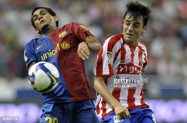 Sporting Gijon's Miguel Marcos Madera 'Michel' vies with FC Barcelona's Brazilian Daniel Alves during their Spanish first league football match at...