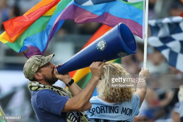 Sporting Kansas City fan yells in a megaphone while flags fly around him during an MLS match between the San Jose Earthquakes and Sporting Kansas...
