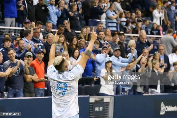 Sporting Kansas City forward Alan Pulido points to the sky after converting a penalty kick in the second half of an MLS match between the Houston...