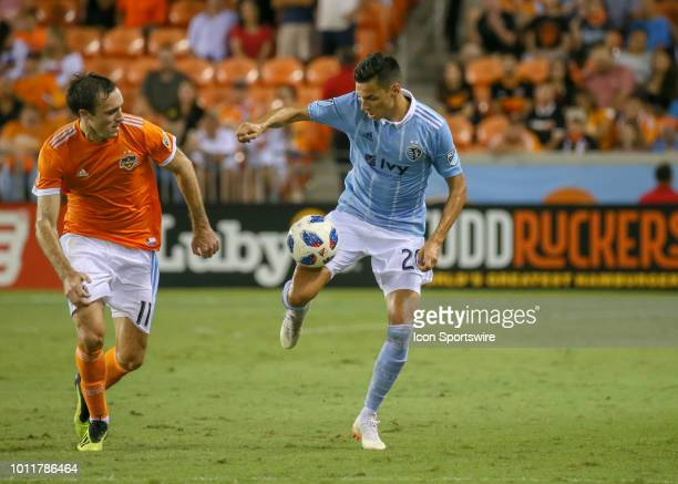 Sporting Kansas City forward Daniel Salloi maintains control of the ball and away from Houston Dynamo forward Andrew Wenger during the soccer match...