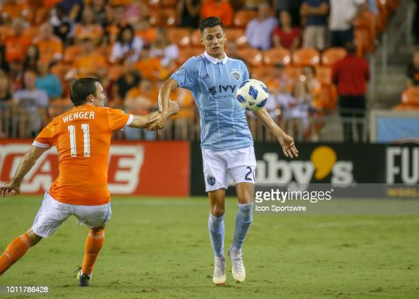 Sporting Kansas City forward Daniel Salloi traps the ball and keeps it away from Houston Dynamo forward Andrew Wenger during the soccer match between...