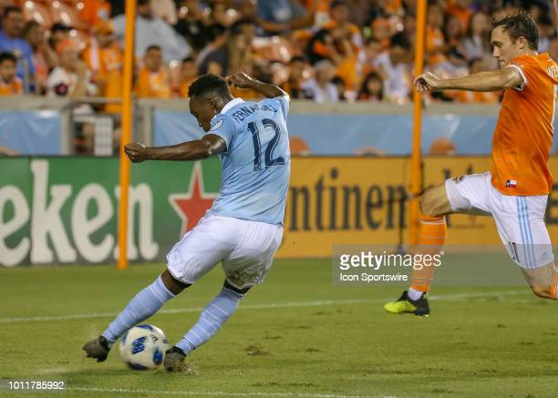 Sporting Kansas City forward Gerso takes a shot on goal as Houston Dynamo forward Andrew Wenger leaps in to intercept the ball during the soccer...