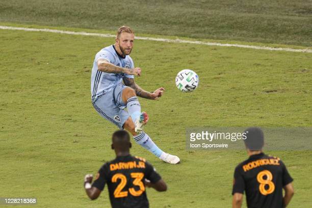 Sporting Kansas City forward Johnny Russell sends a free kick over Houston Dynamo defenders in the second half of an MLS match between the Houston...