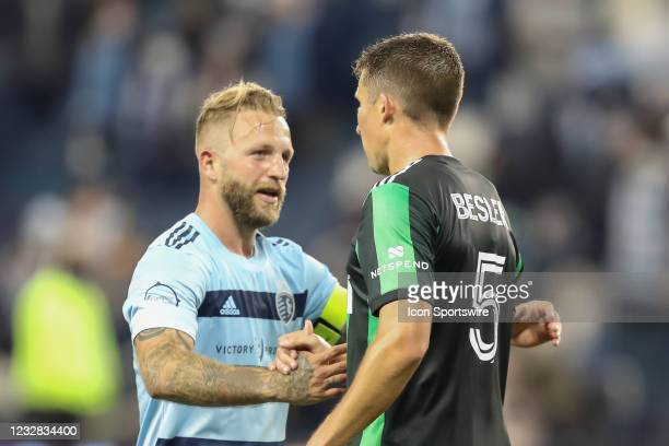 Sporting Kansas City forward Johnny Russell shakes hands with former teammate and current Austin FC defender Matt Besler after an MLS match between...
