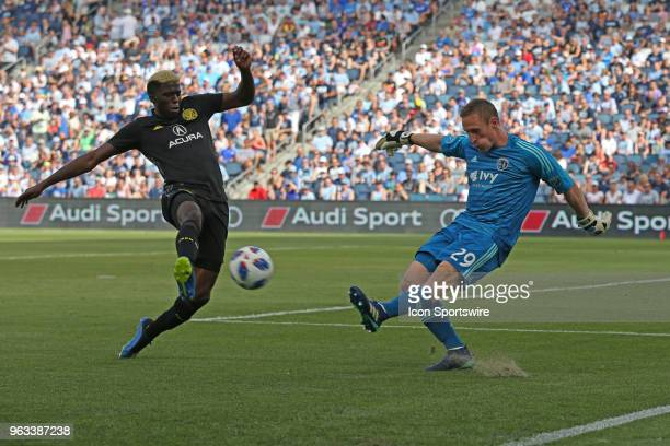Sporting Kansas City goalkeeper Tim Melia clears the ball just past Columbus Crew forward Gyasi Zerdes in the first half of an MLS match between the...