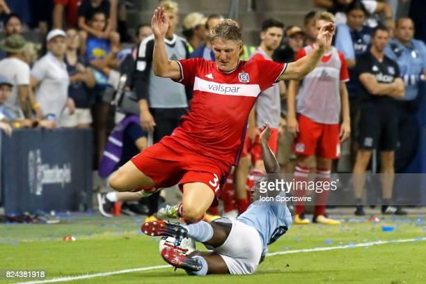 Sporting Kansas City midfielder Jimmy Medranda makes a sliding tackle against Chicago Fire midfielder Bastian Schweinsteiger in the second half of an...