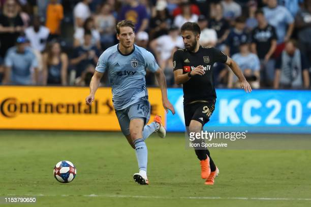 Sporting Kansas City midfielder Nicolas Hasler gets past Los Angeles FC forward Diego Rossi in the first half of an MLS match between LAFC and...