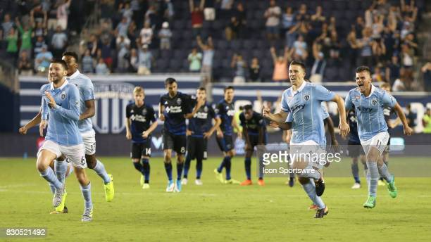 Sporting KC players rush to celebrate with goalkeeper Tim Melia after he stopped a penalty kick to win the Lamar Hunt US Open Cup semifinal against...