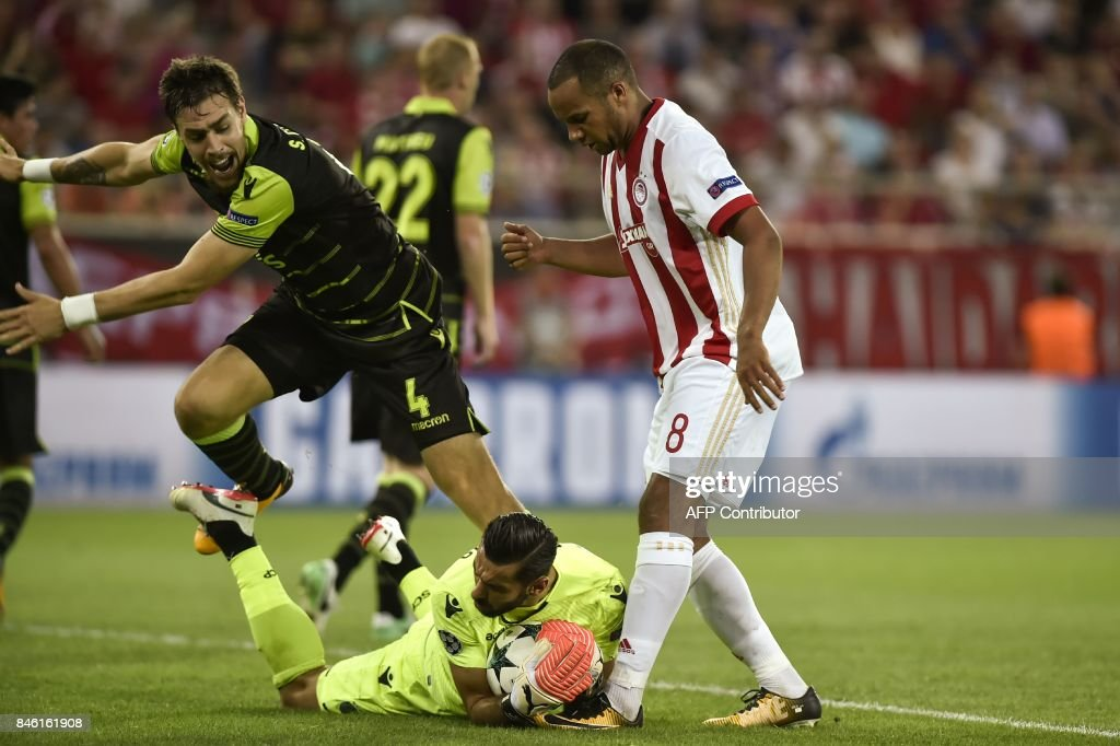 Sporting Lisbon's goalkeeper Rui Patricio (Bottom) grabs the ball in the feet of Olympiacos' Belgian midfielder Vadis Odjida Ofoe (R) as Sporting Lisbon's Uruguayan defender Sebastian Coates looks on during the UEFA Champions League Group D football match between Olympiacos Piraeus FC and Sporting Lisbon on September 12, 2017 at the Karaiskaki stadium in Athens. /