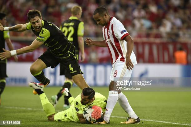 Sporting Lisbon's goalkeeper Rui Patricio grabs the ball in the feet of Olympiacos' Belgian midfielder Vadis Odjida Ofoe as Sporting Lisbon's...