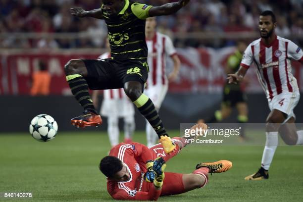 Sporting Lisbon's Ivorian forward Seydou Doumbia jumps over Olympiacos' goalkeeper Stefanos Kapino during the UEFA Champions League Group D football...