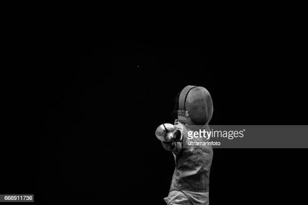 sporting mulheres praticando esgrima esporte mulheres no esporte mulher nova ação do esgrimista no pose de cerco fundo preto bw - esgrima esporte de combate - fotografias e filmes do acervo