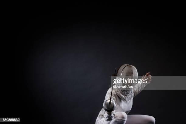 sportieve vrouwen schermen sport beoefenen sport vrouwen in jonge vrouw fencer actie in schermen pose donkere grijze achtergrond - degenschermen stockfoto's en -beelden