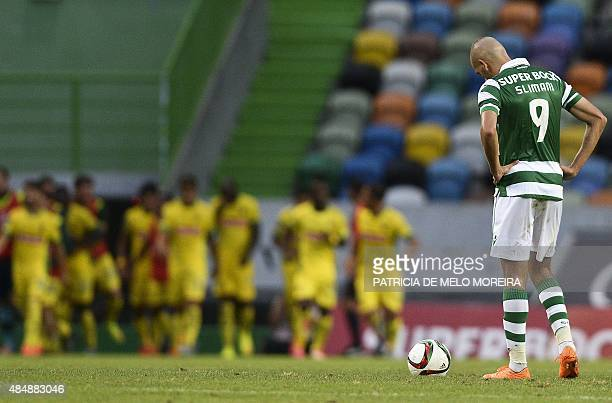 Sporting's Algerian forward Islam Slimani stands on the field after Pacos de Ferreira's midfielder Pele scored during the Portuguese league football...