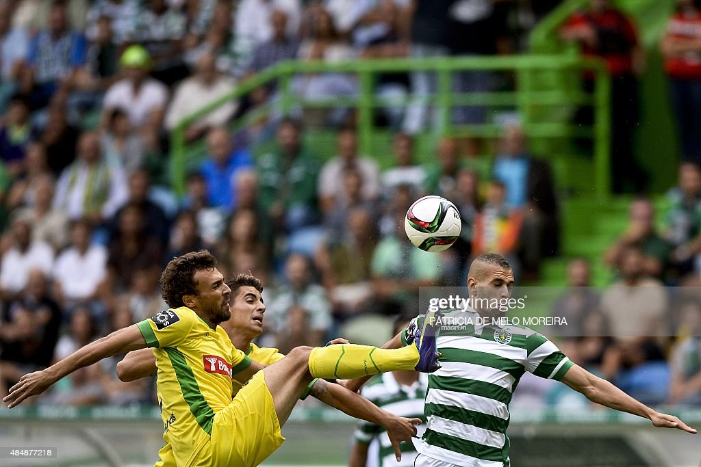 Sporting's Algerian forward Islam Slimani (R) vies with Pacos de Ferreira's defender Marco Baixinho (L) during the Portuguese league football match Sporting CP vs FC Pacos de Ferreira at the Jose Alvalade stadium in Lisbon on August 22, 2015.