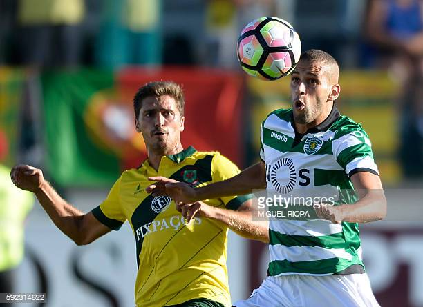 Sporting's Algerian forward Islam Slimani vies with Pacos de Ferreira's defender Filipe Ferreira during the Portuguese league football match FC Pacos...