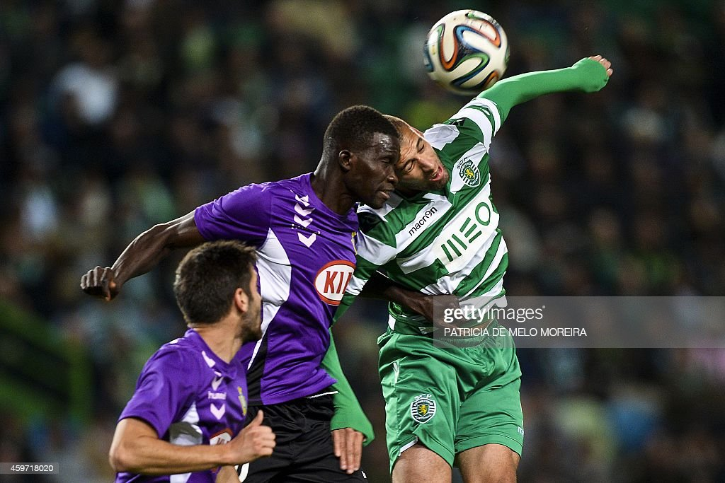 Sporting's Algerian forward Islam Slimani (R) vies with Setubal's Senegalese defender Adama Francois (C) during the Portuguese league football match Sporting vs Vitoria FC at Alvalade stadium in Lisbon on November 29, 2014.