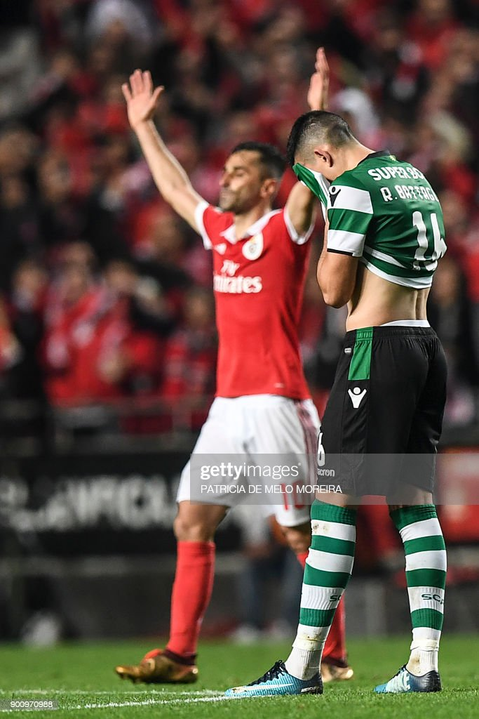Sporting's Argentinian midfielder Rodrigo Battaglia (R) gestures as Benfica's Brazilian forward Jonas Oliveira celebrates during the Portuguese league football match SL Benfica vs Sporting CP at the Luz stadium in Lisbon on January 3, 2018. /