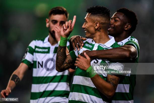Sporting's Brazilian forward Raphinha celebrates his goal with teammates Sporting's Portuguese midfielder Bruno Fernandes and Sporting's Malayan...