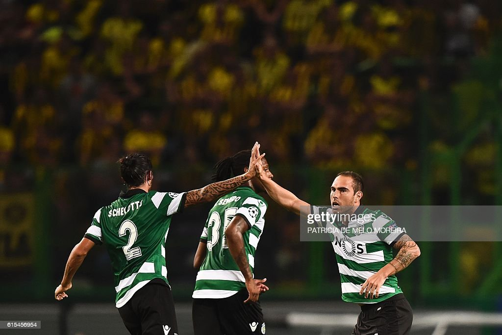 Sporting's Brazilian midfielder Bruno Cesar (R) celebrates with his teammate Sporting's Italian defender Matias Schelotto (L) after scoring during the UEFA Champions League football match Sporting CP vs BVB Borussia Dortmund at the Jose Alvalade stadium in Lisbon on October 18, 2016. / AFP / PATRICIA