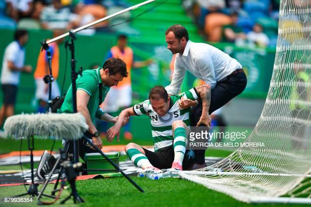 Sporting's Brazilian midfielder Bruno Cesar is attended by medics after scoring a goal during the Portuguese league football match Sporting CP vs OS...