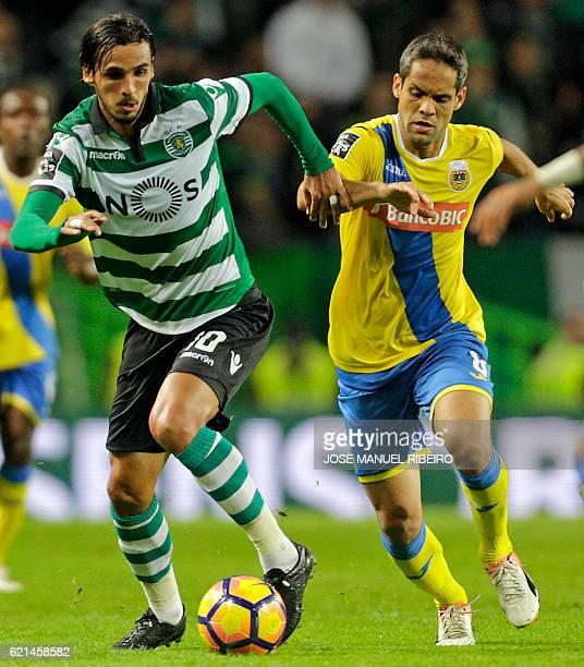 Sporting's Costa Rican forward Bryan Ruiz vies with Arouca's Brazilian midfielder Adilson Filho during the Portuguese league football match Sporting...