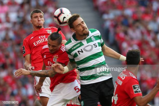 Sporting's defender Sebastian Coates from Uruguay vies with Benfica's Serbian midfielder Ljubomir Fejsa and Portuguese defender Ruben Dias during the...