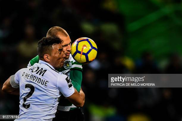 TOPSHOT Sporting's Dutch forward Bas Dost heads the ball with Guimaraes' Brazilian defender Pedro Henrique during the Portuguese League football...