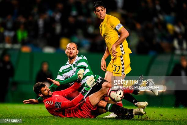 Sporting's Dutch forward Bas Dost vies with Nacional's Brazilian goalkeeper Daniel Guimaraes during the Portuguese League football match between...