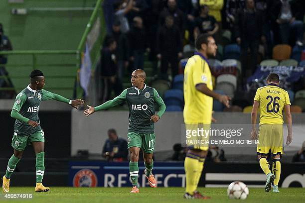 Sporting's forward Carlos Mane celebrates with his teammate midfielder Joao Mario after scoring during the UEFA Champions League football match...