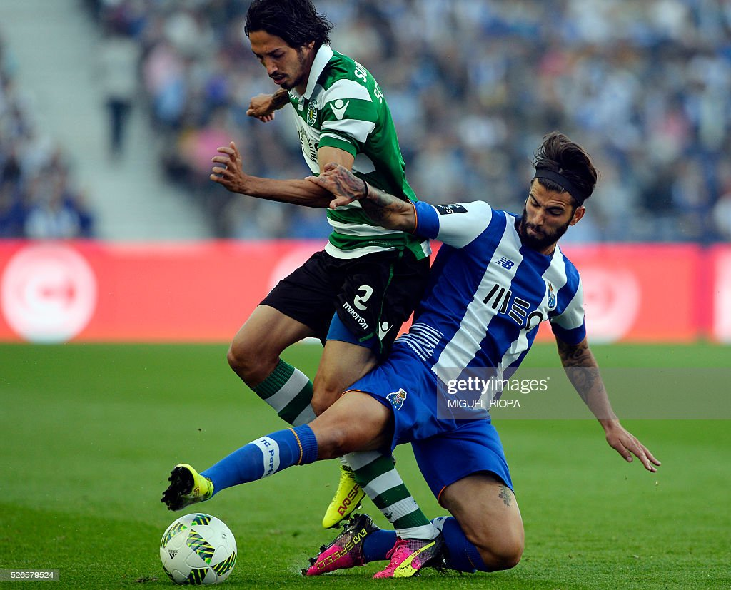 Sporting's Italian defender Ezequiel Schelotto (L) vies with Porto's midfielder Sergio Oliveira during the Portuguese league football match FC Porto vs Sporting CP at the Dragao stadium in Porto on April 30, 2016. / AFP / MIGUEL