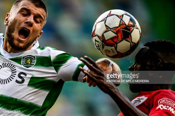 Sporting's Macedonian defender Stefan Ristovski heads the ball with Santa Clara's Nigerian defender Zaidu Sanusi during the Portuguese League...