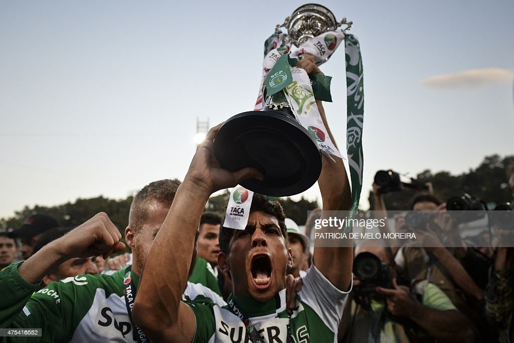 Sporting's midfielder Andre Martins holds the trophy as he celebrates the victory after the Taca de Portugal (Portuguese Cup) football match final Sporting CP vs SC Braga at Jamor stadium in Oeiras, outskirts of Lisbon on May 31, 2015. Sporting won after penalty session by 3-2.