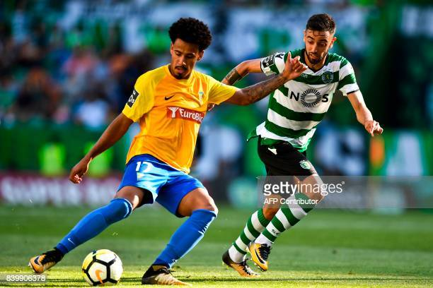 Sporting's midfielder Bruno Fernandes vies with Estoril's Brazilian midfielder Lucas Evangelista during the Portuguese league football match Sporting...