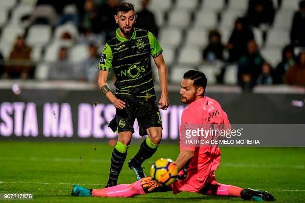 Sporting's midfielder Bruno Fernandes vies with Vitoria Setubal's goalkeeper Cristiano Figueiredo during the Portuguese league football match between...