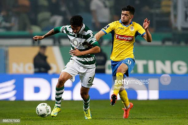 Sporting's midfielder Ezequiel Schelotto vies for the ball with Arouca's forward Ivo Rodrigues during the Portuguese League football match between...