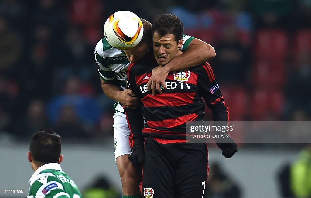 TOPSHOT - Sporting's midfielder Joao Mario vies with Leverkusen's Mexican striker Javier Hernandez during the UEFA Europa League, Round of 32 match football between Bayer Leverkusen and Sporting Lisbon in Leverkusen, western Germany on February 25, 2016. / AFP / PATRIK