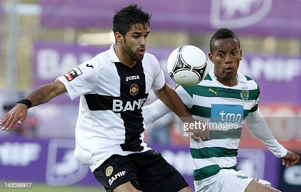 Sporting's Peruan forward Andre Carillo vies with Nacional's forward Daniel Candeias during their Portuguese football match at Madeira Stadium in...