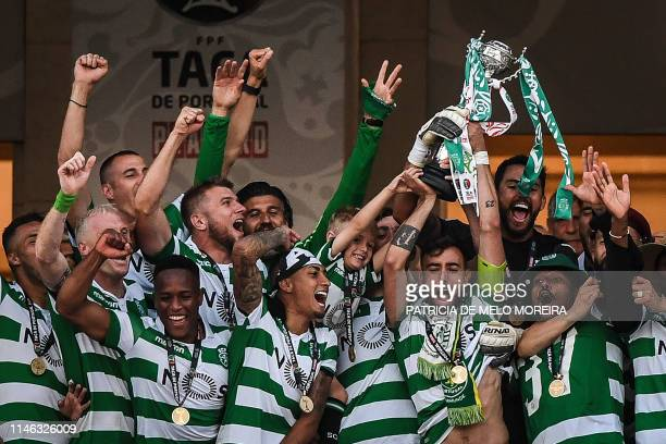 Sporting's players hold up their trophy after winning the Portugal's Cup final football match between Sporting CP and FC Porto at Jamor stadium in...