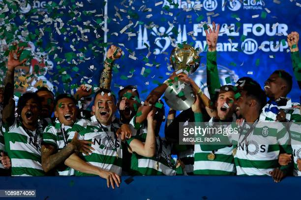 Sporting's players raise the trophy after winning the Portuguese Taca da Liga or League Cup final football match against Porto at the Braga stadium...