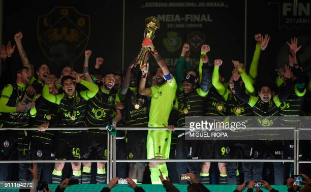 Sporting's Portuguese goalkeeper Rui Patricio holds the trophy as he celebrates with teammates after winning the Portuguese Cup final football match...