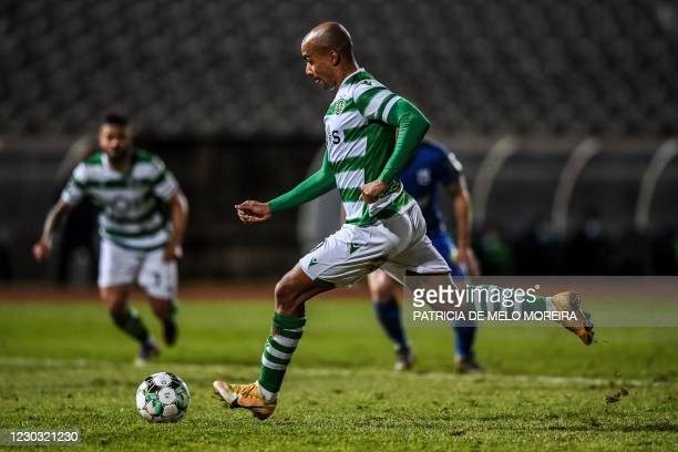 Sporting's Portuguese midfielder Joao Mario shoots a penalty kick and scores a goal during the Portuguese league football match between Belenenses...