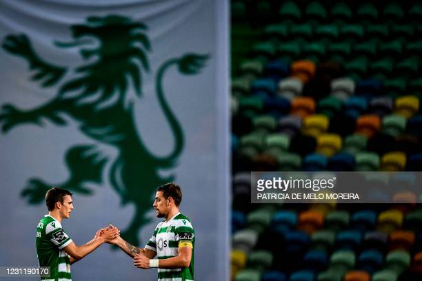 Sporting's Portuguese midfielder Joao Palhinha and teammate Sporting's Uruguayan defender Sebastian Coates celebrate their victory at the end of the...