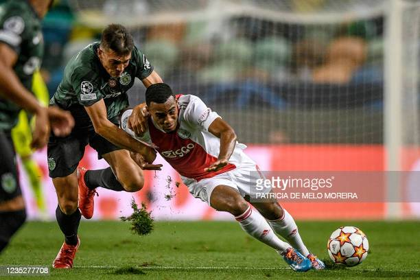 Sporting's Portuguese midfielder Joao Palhinha challenges Ajax's Dutch midfielder Ryan Gravenberch during the UEFA Champions League first round group...