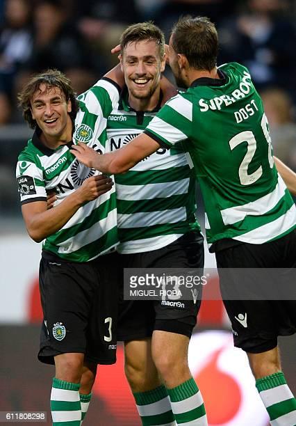 Sporting's Uruguayan defender Sebastian Coates celebrates wiyth teammates Serbian forward Lazar Markovic and Dutch forward Bas Dost after scoring a...