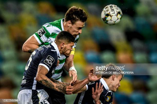 Sporting's Uruguayan defender Sebastian Coates heads the ball with Famalicao's Brazilian defender Riccieli Junior during the Portuguese League...