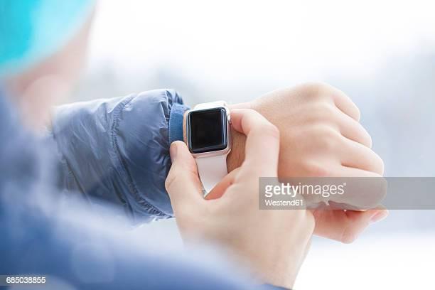 sportive man checking his smartwatch in winter, close-up - スマートウォッチ ストックフォトと画像