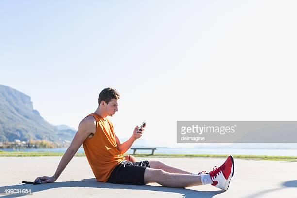 Sportive man checks his smartphone